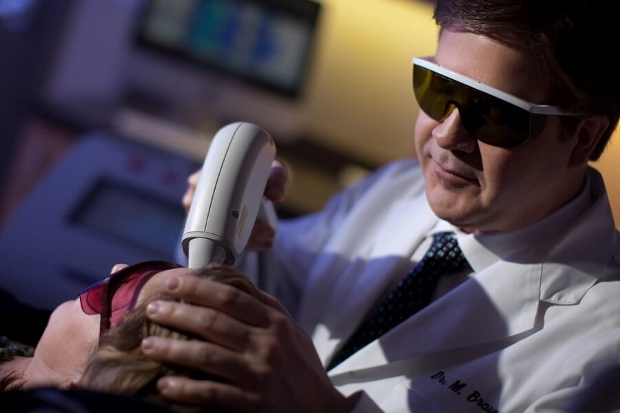doctor using a laser to lighten a patient's skin