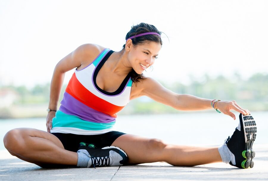 woman smiling while stretching somewhere outside