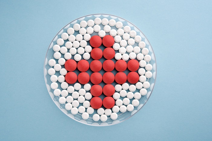 aspirin tablets next to red tablets in the shape of the red cross