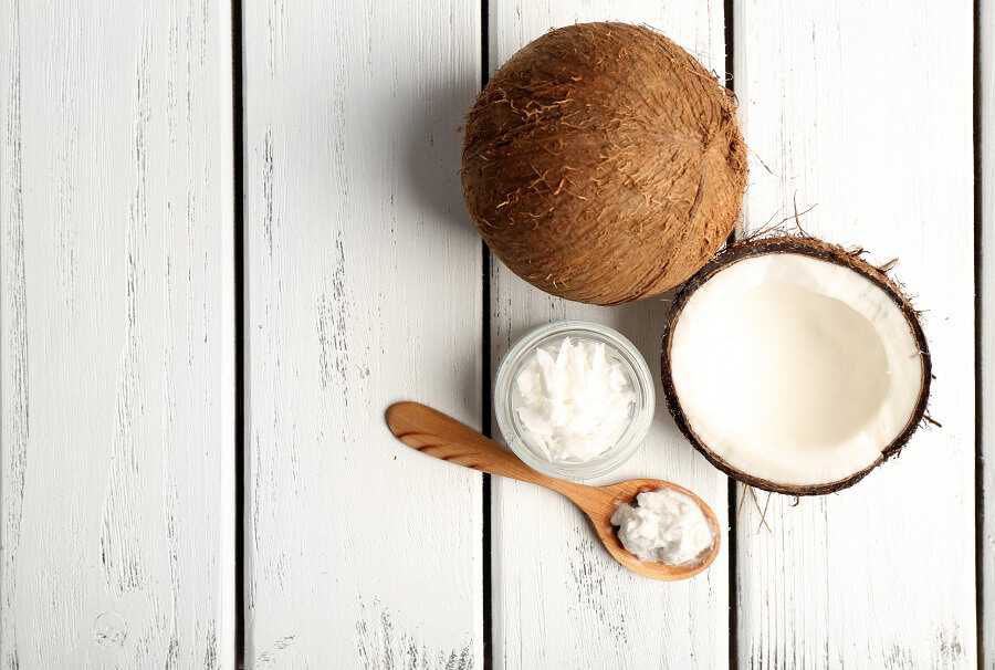 whole coconut next to some coconut oil in solid form