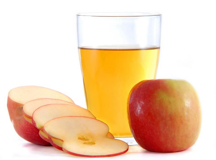 a glass of apple cider vinegar placed next to a whole apple and a sliced one