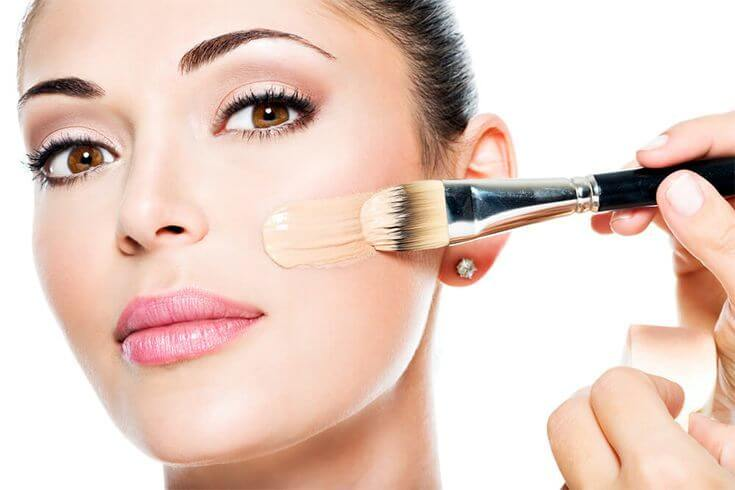 woman applying liquid foundation using a brush