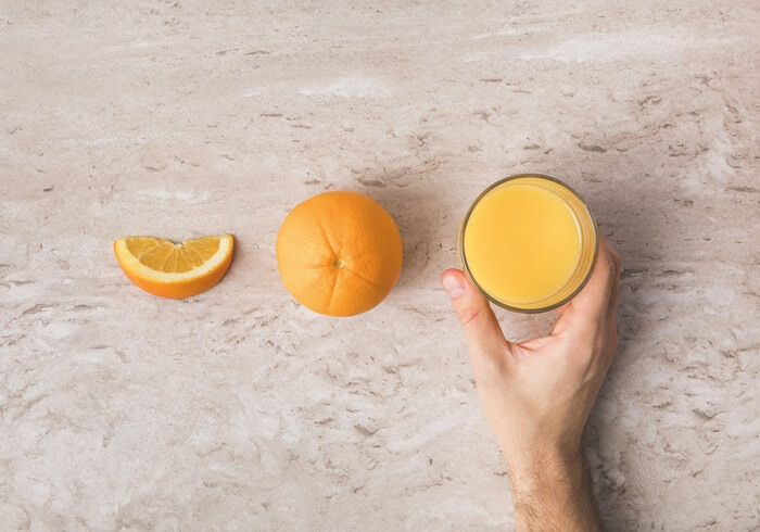 Cropped image of man taking glass of fresh orange juice from table