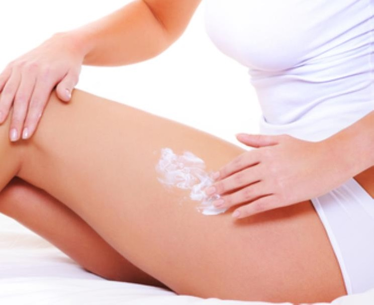 woman applying cream to her leg