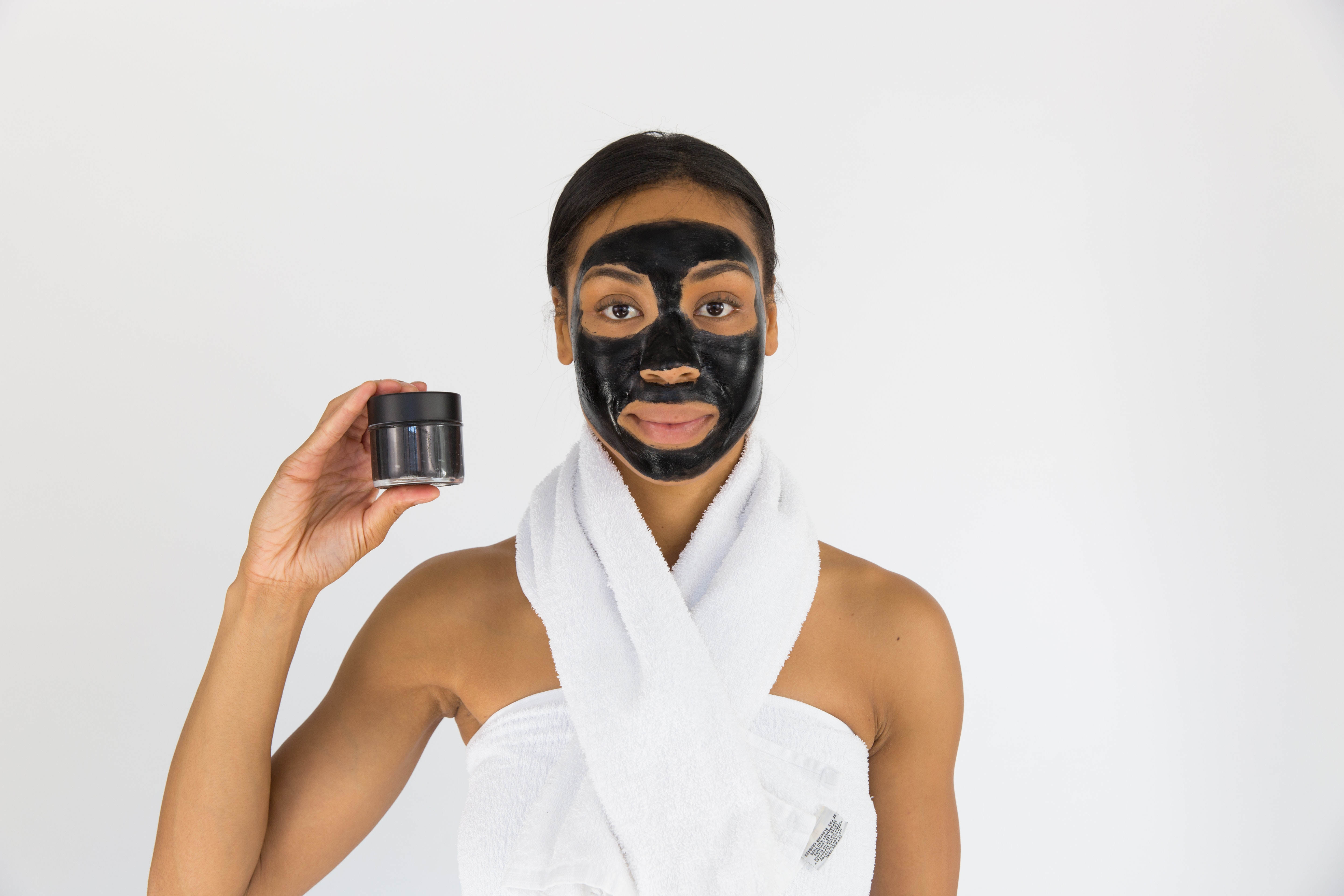 Girl with a Black facial mask was holding a product